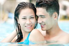 Enjoying swimming. Young happy couple swimming together Stock Images