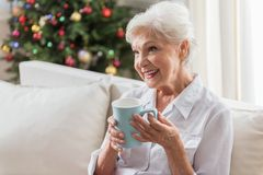 Positive elderly lady is relaxing on couch Stock Photos