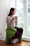 Enjoying tea by the window Royalty Free Stock Photo
