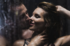 Enjoying their romance. Shot of a beautiful young couple kissing in the shower Stock Photography