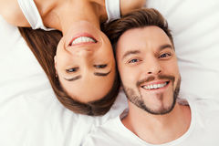 Enjoying their time together. Top view of beautiful young loving couple lying in bed together and smiling Royalty Free Stock Photos