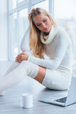 Enjoying time at home. Beautiful young woman in white sweater and socks holding hand in hair and looking at laptop while sitting near the window at home Stock Photos