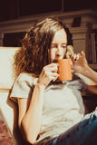 Enjoying time at home. Close up portrait chestnut hair woman relaxing in comfortable chair at window drinking tea or coffee. Natur Royalty Free Stock Photos