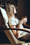 Enjoying time at home. Close up portrait woman relaxing in comfortable modern chair near window holding mug of tea or coffee. Natu Royalty Free Stock Image