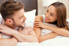 Enjoying time together. Beautiful young loving couple lying in bed together and looking at each other with smile Royalty Free Stock Photography