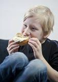 Enjoying a traditional swedish cream bun (semla). Young boy eating a traditional swedish cream bun Royalty Free Stock Images