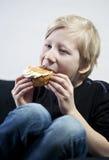 Enjoying a traditional swedish cream bun (semla). Young boy eating a traditional swedish cream bun Stock Images
