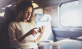 Enjoying travel concept. Young pretty woman tourist traveling by the train sitting near the window using smartphone. stock photo