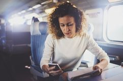 Enjoying travel concept. Young pretty woman tourist traveling by the train sitting near the window using smartphone. stock photos