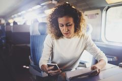Enjoying travel concept. Young pretty woman tourist traveling by the train sitting near the window using smartphone. stock photography