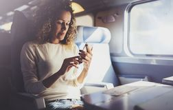 Enjoying travel concept. Young pretty woman tourist traveling by the train sitting near the window using smartphone. royalty free stock photo
