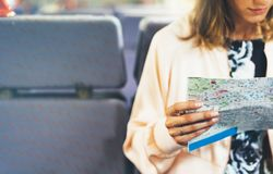Enjoying travel. Young hipster smile girl with backpack traveling by train sitting near the window holding in hand and looking map stock photos
