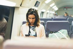Enjoying travel. Young pretty woman traveling by train sitting near the window using smartphone and looking map. Tourist texting royalty free stock photos