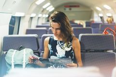 Enjoying travel. Young pretty woman traveling by train sitting near the window using smartphone and looking map. Tourist texting stock photography