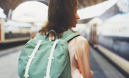 Enjoying travel. Young woman waiting on the station platform with backpack on background electric train. Tourist plan route. Of railway, railroad transport royalty free stock images