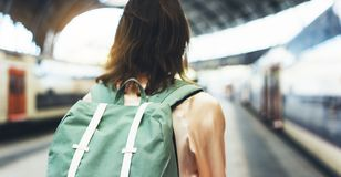 Enjoying travel. Young woman waiting on the station platform with backpack on background electric train. Tourist plan route. Of railway, railroad transport stock image