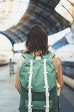 Enjoying travel. Young woman waiting on the station platform with backpack on background electric train. Tourist plan route. Of railway, railroad transport royalty free stock photography