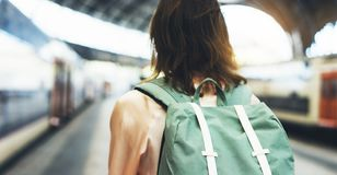 Enjoying travel. Young woman waiting on the station platform with backpack on background electric train. Tourist plan route. Of railway, railroad transport royalty free stock image