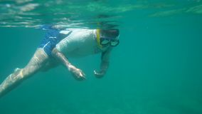 Enjoying the turquoise water of the sea. A shot of a man wearing a snorkeling mask and a white diving garment swimming on a turquoise sea stock video footage