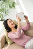 Enjoying tv show. Pretty Chinese woman lying on sofa and watching video on her phone Royalty Free Stock Image