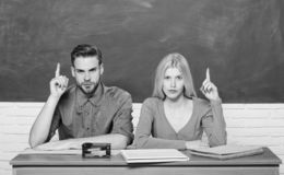 Enjoying university life. Guy and girl sit at desk in classroom. Correct answer on their mind. Studying in college or. University. Apply for free program stock image