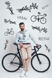 Enjoying urban lifestyle. Full length of stylish young man leaning on his bicycle against grey background with hand. Drawn doodles on it. Urban style. City life stock image