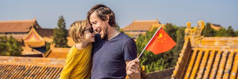 Enjoying vacation in China. Happy family with national chinese flag in Forbidden City. Travel to China with kids concept. Visa free transit 72 hours, 144 hours royalty free stock image
