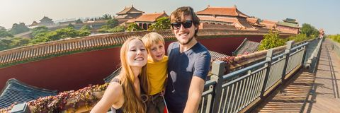 Enjoying vacation in China. Happy family with national chinese flag in Forbidden City. Travel to China with kids concept. Visa free transit 72 hours, 144 hours royalty free stock photos