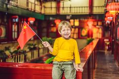 Enjoying vacation in China. Happy tourist boy with a Chinese flag on a Chinese background. Travel to China with kids. Concept. Visa free transit 72 hours, 144 royalty free stock images