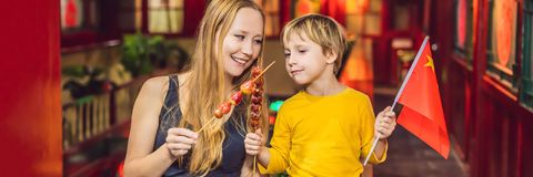 Enjoying vacation in China. Happy tourists mom and son with a Chinese flag and with traditional Chinese candied fruits royalty free stock image