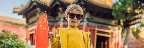 Enjoying vacation in China. Young boy with national chinese flag in Forbidden City. Travel to China with kids concept. Visa free transit 72 hours, 144 hours in stock images