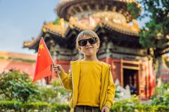 Enjoying vacation in China. Young boy with national chinese flag in Forbidden City. Travel to China with kids concept. Visa free transit 72 hours, 144 hours in royalty free stock image