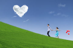 Enjoying Valentine day together in park. Happy couple running enjoying Valentine day together in park under blue sky Royalty Free Stock Photos
