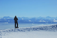 Enjoying the view. A skier, high on a ridge in the Swiss Jura mountains in winter, takes a break from skiing and gazes across to the French Alps. The jagged row Stock Photo