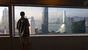 Enjoying the View. A man stands high above the busy streets of Hong Kong and enjoys the expansive vista of the bay and surrounding modern buildings