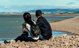 Enjoying the view. Happy young couple in love relaxing in a  beach of Minehead, UK  enjoying ocean view together sitting in the sand embracing and hugging Royalty Free Stock Images