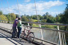Enjoying the View.psd. A couple in their forties take a break on the bike bridge overlooking Alton Baker Park in Eugene Oregon on a beautiful sunny day royalty free stock photos