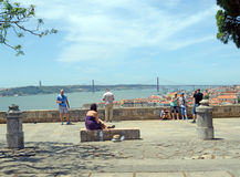Enjoying the View from Saint George Castle, Lisbon. Tourists at Saint George's Castle with a view of the 25th of April Bridge royalty free stock photo