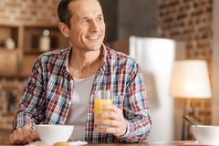 Happy man drinking orange juice at breakfast. Enjoying vitamins. Pleasant young man sitting at the kitchen table, drinking orange juice and looking at the Royalty Free Stock Images