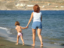 Enjoying a walk on the Beach. A little girl and her mother taking a walk on the beach royalty free stock photo