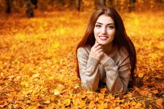 Enjoying warm autumn. A portrait of a beautiful young woman lying on the ground with golden autumn leaves. Lifestyle, autumn fashion, beauty royalty free stock images