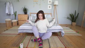 Enjoying a warm knitted woolen sweater sitting next to the bed in a Scandinavian interior. Attractive woman in home. Clothes in her bedroom 4k stock video