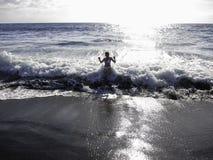 Enjoying the waves hitting the volcanic beach. Enjoying the waves hitting black sand beach in volcanic island of Reunion Stock Photos
