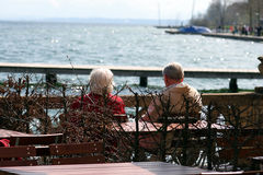 Enjoying the weather. Aged couple sitting at the lake and enjoying the weather Stock Images