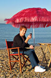 Enjoying wine on beach under parasol. Photo of a happy pensioner enjoying a glass of red wine on beach under parasol Stock Images