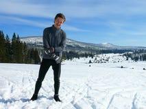 Enjoying winter season. Young man Enjoying winter season, happiness on the snow, snowy hills on the background stock images