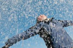Enjoying winter - woman throwing snow Stock Images