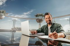 Handsome bearded man sitting at the table with laptop and smiling stock image