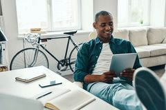 Enjoying working day. Handsome young African man in shirt using digital tablet and smiling while sitting in the office royalty free stock photos