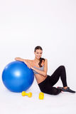 Enjoying workout with her fitness ball and dumbbells. Portrait of young girl leaning on pilates ball and giving you an attractive smile over white isolated Stock Image